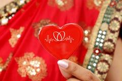 Mujer india tradicional que lleva a cabo forma roja del corazón Fotos de archivo libres de regalías