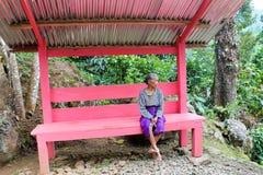 Mujer indonesia mayor que se sienta en un banco rosado imagenes de archivo