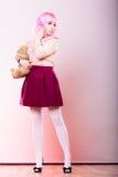 Mujer infantil con el juguete del oso de peluche Imágenes de archivo libres de regalías
