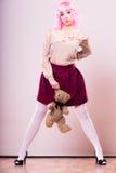 Mujer infantil con el juguete del oso de peluche Fotos de archivo