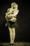 Mujer infantil con el juguete del perro en negro Fotografía de archivo