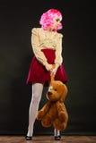 Mujer infantil con el juguete del perro en negro Imagen de archivo libre de regalías
