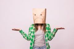 Mujer infeliz con el emoticon triste delante de la bolsa de papel en su cabeza en el fondo blanco fotos de archivo