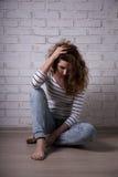 Mujer infeliz con la depresión o headcahe que se sienta en el piso o Fotos de archivo libres de regalías