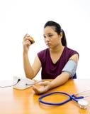 Mujer infeliz con la prueba de la presión arterial imágenes de archivo libres de regalías