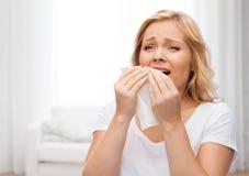 Mujer infeliz con la servilleta de papel que estornuda Imagenes de archivo