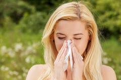 Mujer infeliz con la servilleta de papel que estornuda Fotografía de archivo