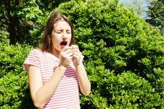 Mujer infeliz con la servilleta que estornuda en el parque verde foto de archivo libre de regalías