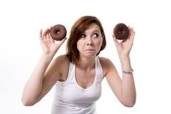 Mujer infeliz del pelo rojo que sostiene los anillos de espuma del chocolate Fotografía de archivo