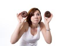 Mujer infeliz del pelo rojo que sostiene los anillos de espuma del chocolate Fotos de archivo