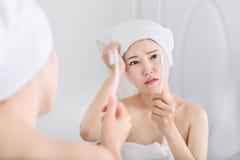 Mujer infeliz en dientes de cepillado de la toalla de baño con el espejo en bathro imagenes de archivo