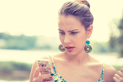 Mujer infeliz escéptica triste trastornada que manda un SMS en el teléfono imágenes de archivo libres de regalías