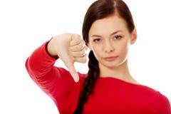 Mujer infeliz joven con el pulgar abajo Imagenes de archivo