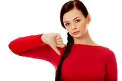 Mujer infeliz joven con el pulgar abajo Fotos de archivo