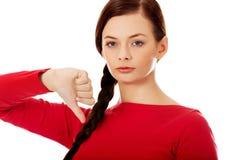 Mujer infeliz joven con el pulgar abajo Imagen de archivo