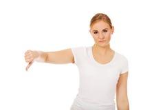 Mujer infeliz joven que muestra el pulgar abajo Imagenes de archivo
