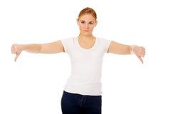 Mujer infeliz joven que muestra el pulgar abajo Foto de archivo libre de regalías
