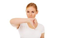 Mujer infeliz joven que muestra el pulgar abajo Fotografía de archivo libre de regalías