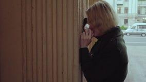 Mujer infeliz que llora cerca de la pared en la ciudad almacen de metraje de vídeo