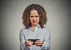 Mujer infeliz que manda un SMS en el teléfono con la cara asqueada Imagen de archivo