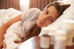 Mujer infeliz que mira la medicación en la mesita de noche Foto de archivo