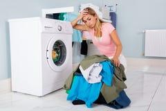 Mujer infeliz que mira la ropa en lavadero Imagen de archivo libre de regalías