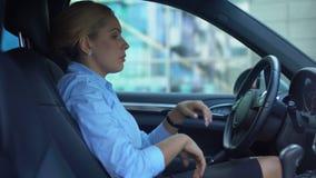 Mujer infeliz que se sienta en el coche, agotado después del día laborable duro, trabajado demasiado almacen de video