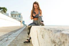 Mujer inhabilitada sonriente del atleta con la pierna prostética imagen de archivo libre de regalías