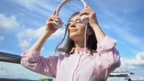 Mujer inspirada que escucha la música en los auriculares, mirando con confianza en futuro almacen de metraje de vídeo