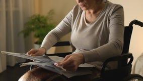 Mujer inteligente en el periódico de la lectura de la silla de ruedas, ocio de la edad avanzada, tiempo libre almacen de metraje de vídeo
