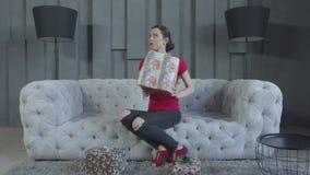 Mujer interesada que elige la caja de regalo para desempaquetar almacen de video