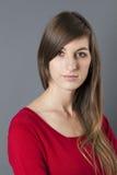 Mujer introvertida 20s con el pelo largo que expresa timidez Fotos de archivo