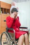 Mujer inválida triste cerca del hombre mayor Fotografía de archivo