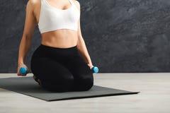 Mujer irreconocible de la aptitud que lleva a cabo pesas de gimnasia en fondo gris Imagenes de archivo