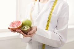 Mujer irreconocible del nutricionista con las frutas en la oficina imagenes de archivo