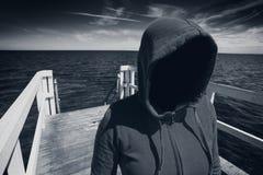 Mujer irreconocible encapuchada anónima en el embarcadero del océano, abducción Co Imagen de archivo libre de regalías