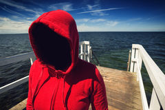Mujer irreconocible encapuchada anónima en el embarcadero del océano, abducción Co Fotos de archivo