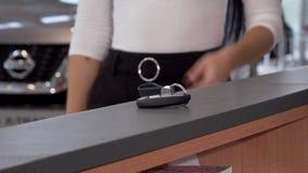 Mujer irreconocible que toma llaves del coche de la tabla en el salón de la representación metrajes