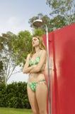 Mujer irritada en el bikini que se coloca debajo de ducha Imagenes de archivo