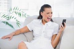 Mujer irritada en el vestido blanco que grita en su smartphone Fotos de archivo libres de regalías
