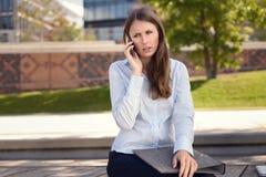 Mujer irritada que frunce el ceño como ella charla en un móvil foto de archivo libre de regalías