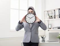 Mujer islámica con el reloj en el espacio de trabajo de la oficina imagen de archivo libre de regalías