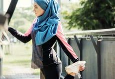 Mujer islámica que estira después de entrenamiento en el parque Imagenes de archivo