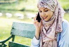 Mujer islámica que usa el teléfono móvil con la sonrisa en el parque Fotografía de archivo