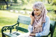 Mujer islámica que usa el teléfono móvil con la sonrisa en el parque Foto de archivo libre de regalías