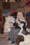 Mujer islámica tradicional que trabaja en una manta Imagen de archivo