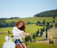 Mujer italiana hermosa joven que se sienta en una vespa foto de archivo