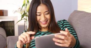 Mujer japonesa feliz que usa la tableta en el sofá imagen de archivo