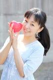 Mujer japonesa joven con el corazón rojo Foto de archivo libre de regalías