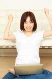 Mujer japonesa joven con el ordenador satisfecha Fotografía de archivo libre de regalías